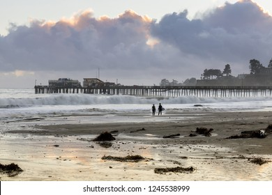 Capitola Beach and wharf in stormy clouds sunset and surfers silhouette. Capitola, Santa Cruz County, California, USA.