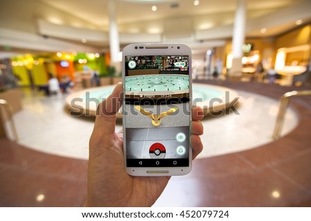 "CAPITOLA, CALIFORNIA - JULY 13, 2016: The hit augmented reality smartphone app ""Pokemon GO"" shows a Pokemon encounter at a mall fountain in the real world."