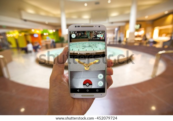 """CAPITOLA, CALIFORNIA - JULY 13, 2016: The hit augmented reality smartphone app """"Pokemon GO"""" shows a Pokemon encounter at a mall fountain in the real world."""