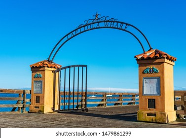 Capitola wharf arch entry welcomes visitors to wooden pier fishing tourist destination on Pacific Ocean - Capitola, California, USA - Circa, 2019