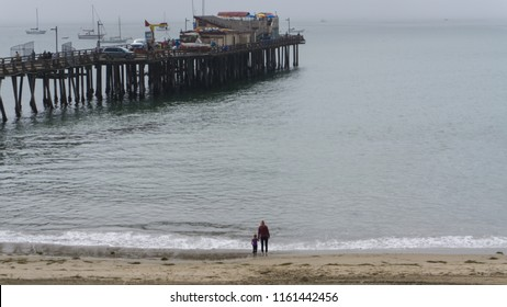 Capitola,CA beach pier with a family looking at oceab