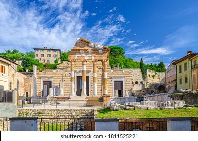 Capitolium of Brixia or Temple of Capitoline Triad or Tempio Capitolino ruins and Santuario Repubblicano, Brescia city historical centre, Cidneo Hill green trees background, Lombardy, Northern Italy
