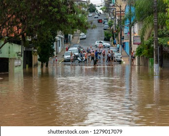 CAPIVARI, SP/BRAZIL - JAN 06, 2019 - People crossing flooded streets - Capivari river overflow Sao Paulo - Brazil