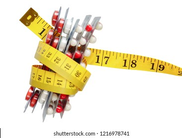 Caplets pack coiled by a tape measure isolated on white