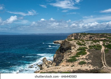 Capo Mannu Cliffs and beach against blue sea or ocean with blue sky and cumulus clouds. Waves crashing against rocks and trail for cars is seen. Shot in Capo Mannu, Mesa Longa beach, Sardinia, Italy.