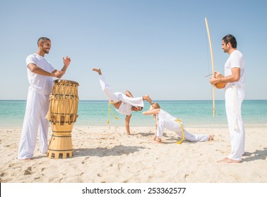 Capoeira team training on the beach - Martial arts athletes performing stunts while two men play music
