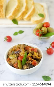 Caponata or ratatouille from a variety of vegetables served with ciabatta and olive.