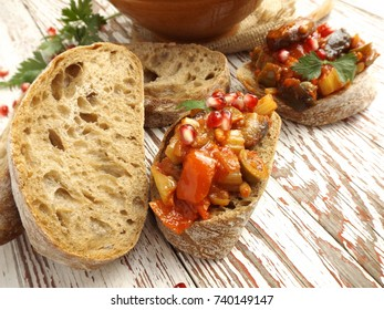 Caponata in Sicilian on slices of ciabatta. Traditional Italian cuisine.