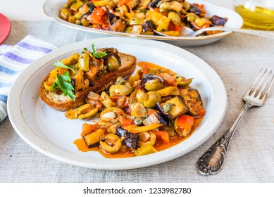 Caponata siciliana on a plate with toast close-up on a rustic background
