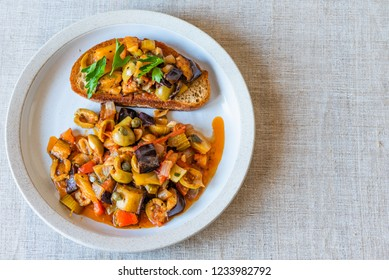Caponata siciliana on a plate with toast close-up, top view, copy space for recipe