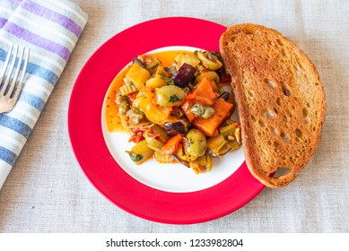 Caponata siciliana on a plate with toast close-up, top view