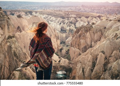 Cappadocia landscape with a women standing from the back on a high cliff. Fairy chimneys panorama that brings inspiration.