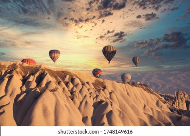Cappadocia/ May 30, 2020: Hot air ballons flying over Cappadocia National Park Göreme Turkey, foggy air. Colorful hot air balloons with over deep canyons, valleys and fairy chimneys