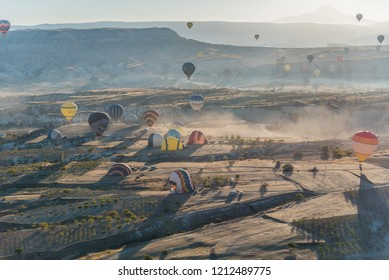 Cappadocia, Turkey - 7th October 2018: Colorful hot air balloons landing on the ground in Cappadocia, Turkey