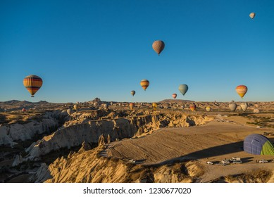 Cappadocia, Turkey - 7th October 2018: Aerial view of numerous hot air balloons flying all over the unique geological features of Cappadocia during the sunrise, Turkey