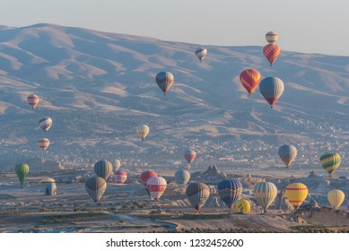 Cappadocia, Turkey - 8th October 2018: Aerial view of numerous hot air balloons taking off to fly all over the unique geological features of Cappadocia during the sunrise from Uchisar, Turkey