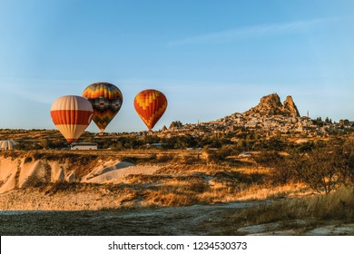Cappadocia, Turkey -  Aerial view of numerous hot air balloons flying all over the unique geological features of Cappadocia during the sunrise, Uchisar castle Nevsehir Turkey