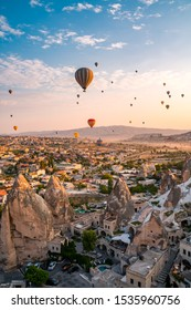 Cappadocia / Turkey - August 01 2019 : Beautiful scenes in Goreme Cappadocia. Hundreds of hot air balloons flying in the sky