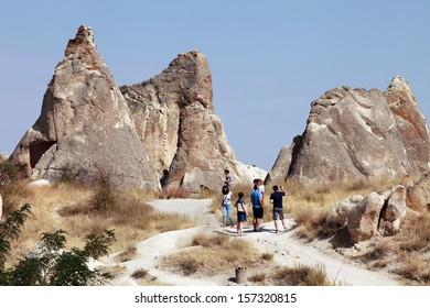 CAPPADOCIA, TURKEY - AUGUST 24: Tourists at Zelve Valley in Cappadocia on September 24, 2013 in Nevsehir, Turkey. Cappadocia is part of the UNESCO World Heritage Site.