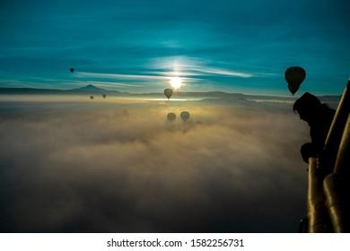 Cappadocia, Turkey / December 25, 2015: Hot air ballons flying over Cappadocia National Park Goreme Turkey, fogyy air