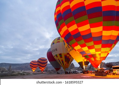Cappadocia, Turkey / January 12, 2020: Hot air balloons starting to take off over spectacular Cappadocia. Beautiful view of colorful hot air balloons floating in sunrise light.