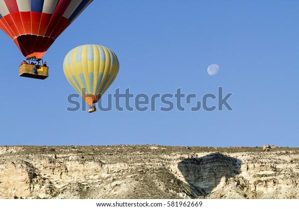 CAPPADOCIA, TURKEY - MAY 18, 2014: Hot air balloons in the sky with the moon in Cappadocia, Turkey