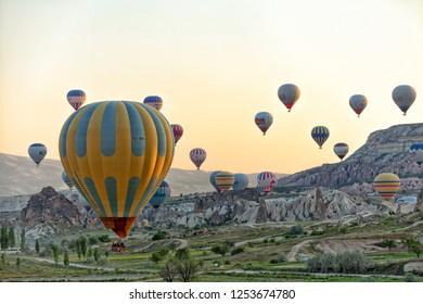 Cappadocia, Turkey, May 3, 2013: Early morning lift off of hot air balloons flying over the landscape at Cappadocia Turkey