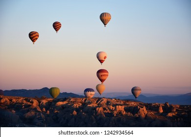 CAPPADOCIA, TURKEY - OCTOBER 27, 2018: Colorful hot air balloons are taking off early in the morning at sunrise