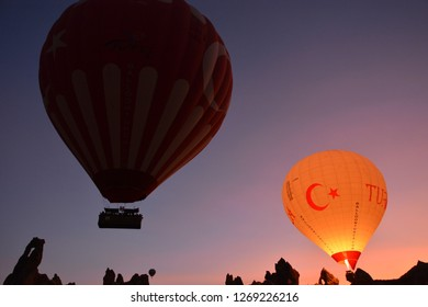 CAPPADOCIA, TURKEY - OCTOBER 27, 2018: Turkish flag themed hot air balloons are taking off early in the morning