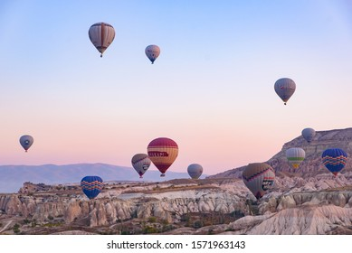 Cappadocia / Turkey - October 30 2019: Flying hot air balloons and rock landscape at sunrise time in Goreme, Cappadocia, Turkey