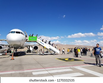 Cappadocia,Turkey-Circa October 2018: Airplane parks at the outdoor terminal of Nevşehir KapadokyaAirport and passengers walk down the stairway to entrance gate by their own.