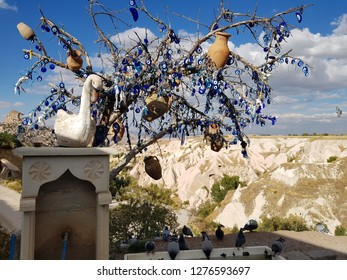 Cappadocia,Turkey-Circa October 2018: Glass amulets with blue eye painted hangs on a tree at Pigeon Valleys, locally called nazar. Local people believe that amulets can protect against the evil eye.
