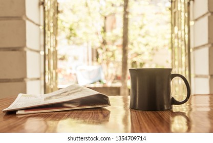 Cappuccino aroma cup of coffee for breakfast in cafe on wooden table background with newspaper. Morning sunlight coming from window on sun day or holiday. Leisure business idea. Copy space room text