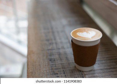 Cappuccino with beautiful heart shape latte art in the paper to-go cup. Take away coffee concept. Wooden rustic background, loft space. Copy space for your text. Side-view