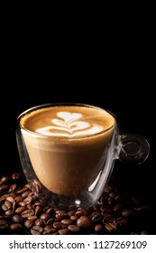Cappuccino with a beautiful pattern of milk on top in a cup of double-sided glass on a black background, beside scattered coffee beans. Background image. Copy space, selective focus