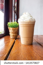 Cappuccino blend with whipping cream in plastic cup. Served on wooden table in cafe. Favorite menu of caffeine beverage.
