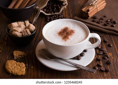 Cappuccino with brown sugar and cinnamon on dark wood