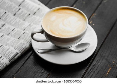 cappuccino in a cafe on the table. morning ritual of coffee with a newspaper.