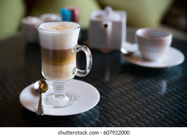 A cappuccino in clear cup showing layer of coffee, milk, and cream