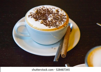 Cappuccino, coffee black, latte macchiato, caffè latte with grated dark chocolate on dark wooden table. Hot drinks with a biscuit cookie and and whipped cream. Quality time with friends or family.