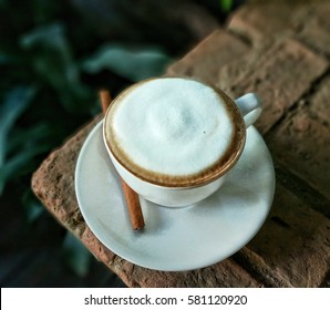 Cappuccino coffee with cinnamon on a cement table on tree blurred background