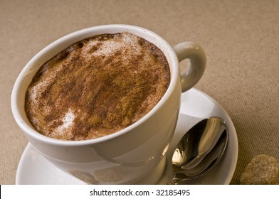 Cappuccino coffee cup with froth over brown background