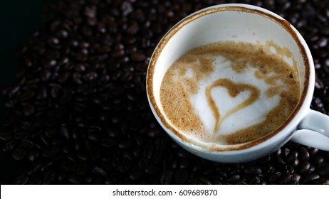 Cappuccino coffee. A cup of latte, cappuccino or espresso coffee with milk put on dark roasting coffee beans. Drawing the hearts from milk on top.