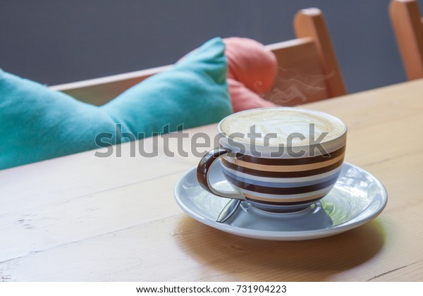 Cappuccino coffee in cup on wooden table