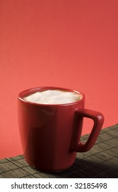 Cappuccino coffee drink with white froth in a red cup