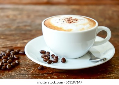 Cappuccino coffee on old wooden table and roasted coffee beans