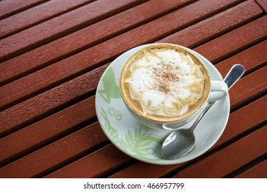 Cappuccino coffee on wood table background in coffee shop