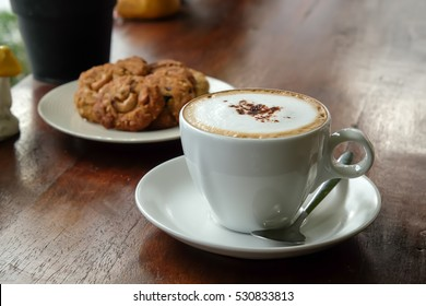 Cappuccino coffee on wood table and bakery background