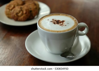 Cappuccino coffee on wood table and bakery background and morning light background