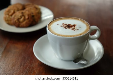 Cappuccino coffee on wooden table and cookies background